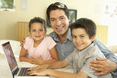 Ordinateur hispanique d'And Children Using de père à la maison Photographie stock libre de droits