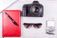 Ordinateur portable, écrivant le carnet, l'appareil-photo et le joueur musical Photos stock