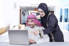 Ordinateur portable arabe d'utilisation de couples à la maison Photo libre de droits