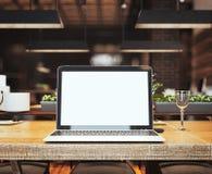 Ordinateur portable argenté à la table dans le restaurant rendu 3d Photos libres de droits