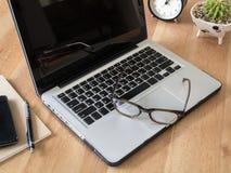 Ordinateur portable avec des lunettes sur le bureau en bois Photos libres de droits