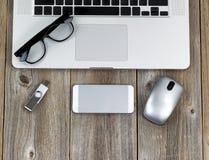 Ordinateur portable avec des périphériques et des verres de lecture sur W rustique Photos stock