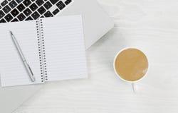 Ordinateur portable avec du café et le bloc-notes vide sur le bureau blanc Image libre de droits