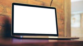 Ordinateur portable avec l'écran blanc vide sur la table en bois en café moderne en bois Image libre de droits
