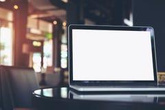 Ordinateur portable avec l'écran blanc vide sur la table en bois dans le café Images stock