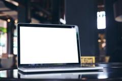 Ordinateur portable avec l'écran blanc vide sur la table en bois dans le café Image libre de droits