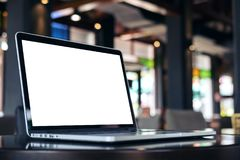 Ordinateur portable avec l'écran blanc vide sur la table en bois dans le café Photos libres de droits