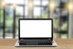 Ordinateur portable avec l'écran blanc vide sur la table en bois de vintage sur le fond moderne brouillé de bureau Images stock