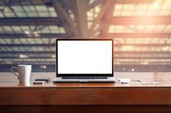 Ordinateur portable avec l'écran blanc vide sur la table et l'espace de travail dans le bureau Image stock