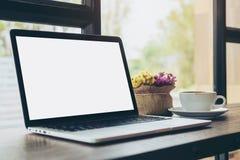 Ordinateur portable avec l'écran blanc vide, une tasse de café et le vase à fleur sur la table en bois en café moderne de grenier Photographie stock libre de droits