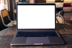 Ordinateur portable avec l'écran de bureau blanc vide sur la table en bois en café moderne Photos stock