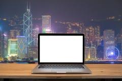 Ordinateur portable avec l'écran vide sur la table backgroun de ville de nuit de Hong Kong photographie stock