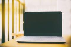 Ordinateur portable avec l'écran vide sur la table fond intérieur, brouillé Photo stock