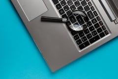 Ordinateur portable avec la loupe sur le fond bleu, concept de recherche Image conceptuelle de s?curit? d'Internet photos stock