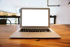 Ordinateur portable avec la moquerie vers le haut de l'écran vide sur la table en bois devant le cof Image stock