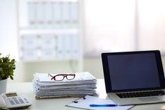 Ordinateur portable avec la pile de dossiers sur la table sur le blanc Photographie stock