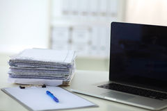 Ordinateur portable avec la pile de dossiers sur la table sur le blanc Image stock