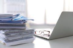 Ordinateur portable avec la pile de dossiers sur la table sur le blanc Image libre de droits