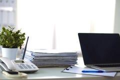 Ordinateur portable avec la pile de dossiers sur la table sur le blanc Photos libres de droits