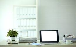 Ordinateur portable avec la pile de dossiers sur la table sur le fond blanc Images stock