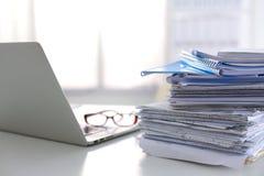 Ordinateur portable avec la pile de dossiers sur la table sur le fond blanc Photo stock