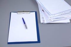 Ordinateur portable avec la pile de dossiers sur la table sur le fond blanc Photos stock