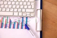 Ordinateur portable avec la pile de dossiers sur la table sur le fond blanc Photo libre de droits