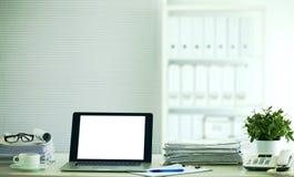 Ordinateur portable avec la pile de dossiers sur la table sur le fond blanc Image stock