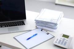 Ordinateur portable avec la pile de dossiers sur la table sur le fond blanc Photographie stock