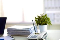 Ordinateur portable avec la pile de dossiers sur la table sur le fond blanc Image libre de droits
