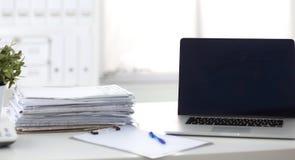Ordinateur portable avec la pile de dossiers sur la table sur le fond blanc Photographie stock libre de droits