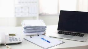 Ordinateur portable avec la pile de dossiers sur la table sur le fond blanc Photos libres de droits