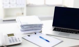 Ordinateur portable avec la pile de dossiers sur la table sur le fond blanc Images libres de droits