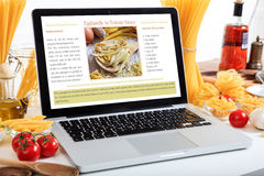 Ordinateur portable avec la recette sur une table avec des pâtes et des légumes Photos stock
