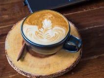 Ordinateur portable avec la table en bois de tasse de café d'art de latte Photos stock