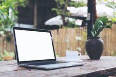 Ordinateur portable avec la tasse blanche vide d'écran et de café sur la table en bois de vintage en parc extérieur de nature images libres de droits