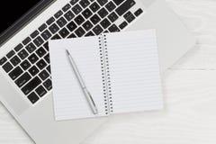 Ordinateur portable avec le bloc-notes vide et stylo sur le bureau blanc Photo libre de droits