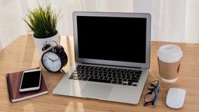 Ordinateur portable avec le carnet de téléphone et la tasse de café intelligents sur la table de lieu de travail Photographie stock