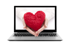 Ordinateur portable avec le coeur rouge chez des mains de la femme Photo stock