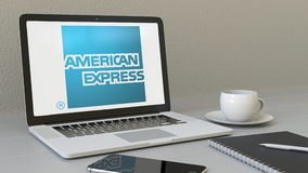 Ordinateur portable avec le logo d'American Express sur l'écran Rendu conceptuel de l'éditorial 3D de lieu de travail moderne Photo libre de droits
