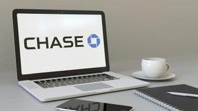 Ordinateur portable avec le logo de JPMorgan Chase Bank sur l'écran Rendu conceptuel de l'éditorial 3D de lieu de travail moderne Photo libre de droits