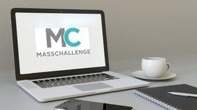 Ordinateur portable avec le logo de MassChallenge sur l'écran Rendu conceptuel de l'éditorial 3D de lieu de travail moderne Image libre de droits
