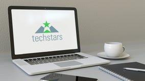 Ordinateur portable avec le logo de Techstars sur l'écran Rendu conceptuel de l'éditorial 3D de lieu de travail moderne Images stock