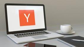 Ordinateur portable avec le logo de Y Combinator sur l'écran Rendu conceptuel de l'éditorial 3D de lieu de travail moderne Photographie stock