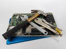 Ordinateur portable avec le marteau, les clés et les pinces de verrouillage Photographie stock