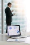 Ordinateur portable avec les diagrammes croissants d'affaires Photographie stock libre de droits