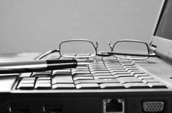Ordinateur portable avec les verres et le stylo de lecture Photos stock