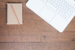 Ordinateur portable blanc avec le carnet sur la table en bois, espace de travail Photo libre de droits