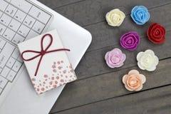 Ordinateur portable, boîte-cadeau et sept roses colorées sur le conseil en bois photo stock
