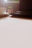 Ordinateur portable, café et fleur sur la table en bois dans un lieu de travail et une lumière du soleil Photo libre de droits